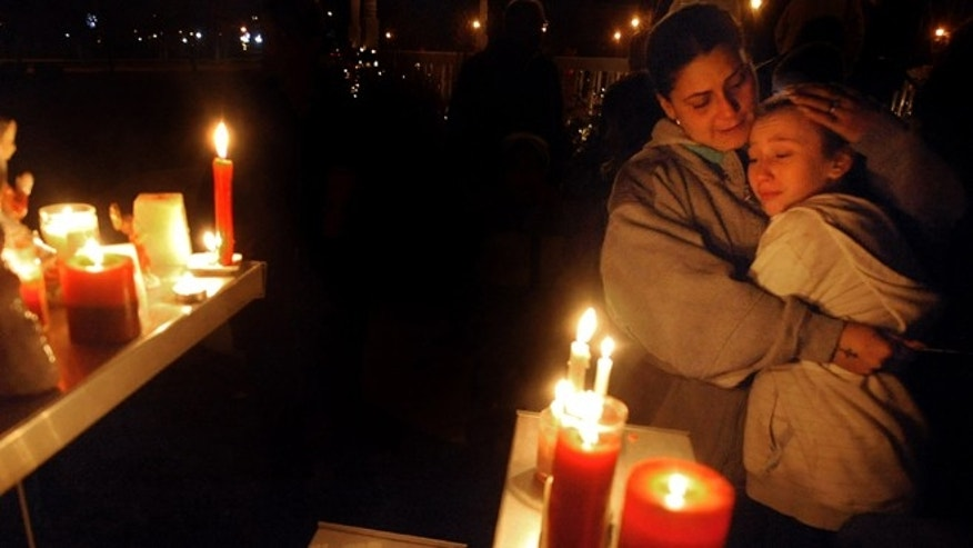 Dec. 14, 2012: Brenda Hernadez of Enfield Conn., comforts her daughter Crystal at a makeshift shrine on the Enfield Town Green, Friday evening, after a candlelight vigil in Enfield, Conn.