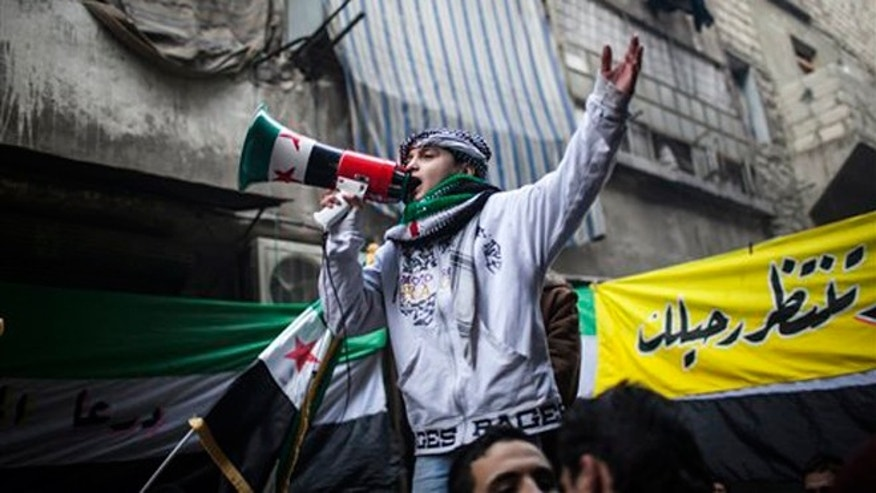 Jan. 4, 2013: A child uses a megaphone to lead others in chanting Free Syrian Army slogans during a demonstration in the neighborhood of Bustan Al-Qasr, Aleppo, Syria. The U.N. said Wednesday that more than 60,000 people have been killed since Syria's crisis began in March 2011 — a figure much higher than previous opposition estimates.