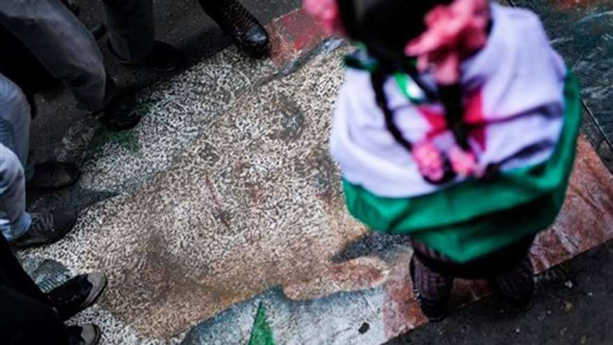 Jan. 4, 2013: Syrians stomp on a portrait during a demonstration in the neighborhood of Bustan Al-Qasr, Aleppo, Syria. The U.N. said Wednesday that more than 60,000 people have been killed since Syria's crisis began in March 2011 — a figure much higher than previous opposition estimates.