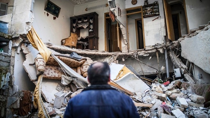 Jan. 3, 2013: A civilian looks at a destroyed home in Aleppo, Syria.