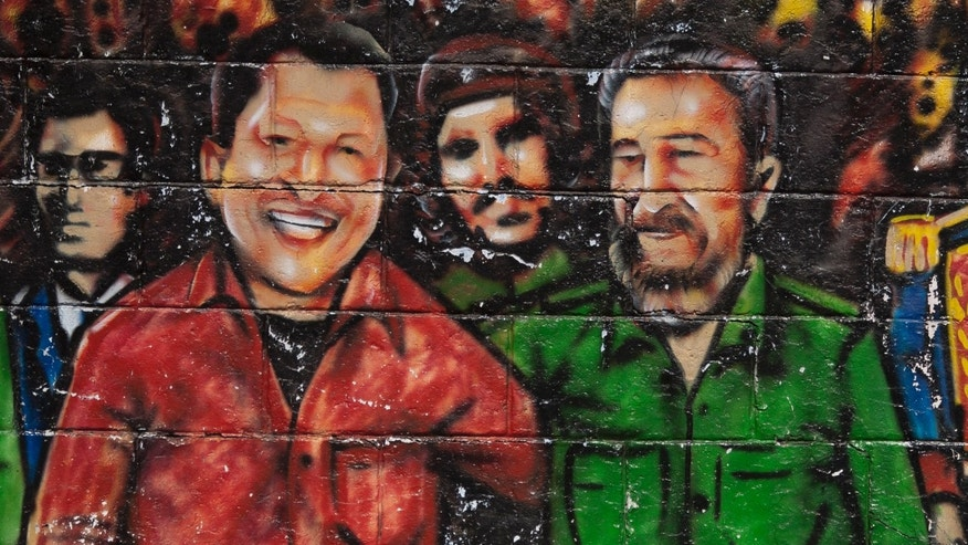 In this Feb. 22, 2012 file photo, a mural featuring Venezuela's President Hugo Chavez, left, and Cuba's Fidel Castro, adorns a wall in Caracas, Venezuela. (AP Photo/Ariana Cubillos, File)