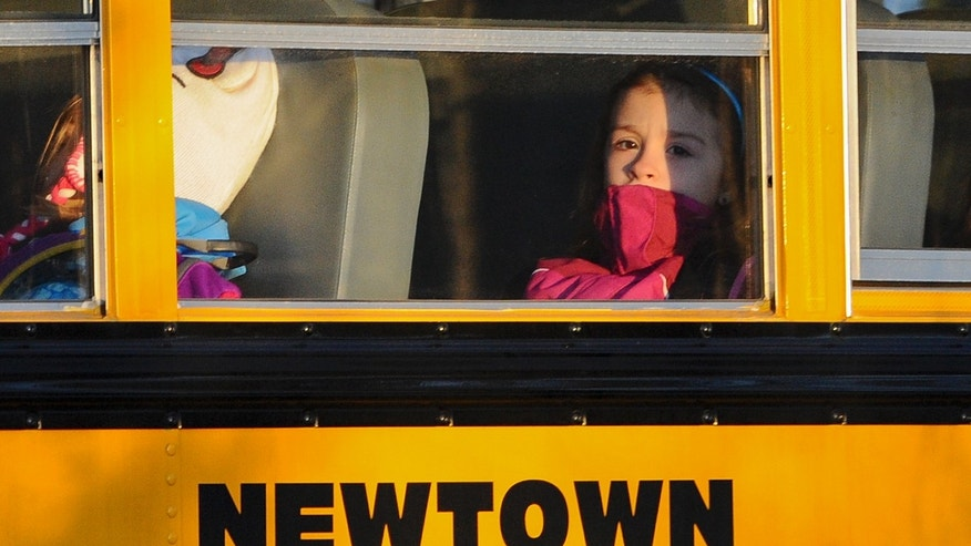 A girl sits on a Newtown bus leaving the new Sandy Hook Elementary School after the first day of classes in Monroe, Conn.