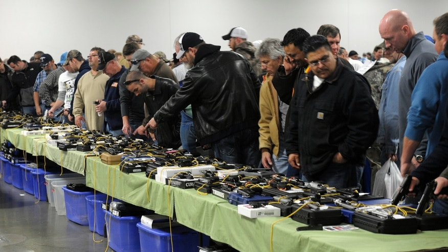 FILE: Dec. 22, 2012: People look over a table of handguns for sale at a gun show in Kansas City, Missouri.
