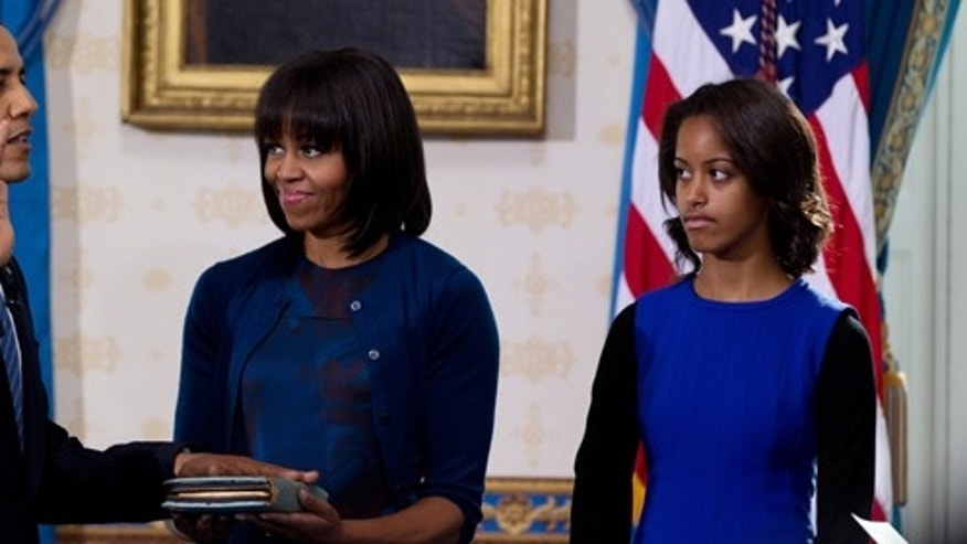 President Obama takes the oath of office at the official swearing-in ceremony in the Blue Room of the White House Sunday, Jan. 20, 2013. Administering the oath is Supreme Court Chief Justice Roberts (not shown). Holding the Bible is first lady Michele Obama and looking on are Obama children Malia and Sasha (not shown).   (Photo by Doug Mills/ The New York Times / POOL)