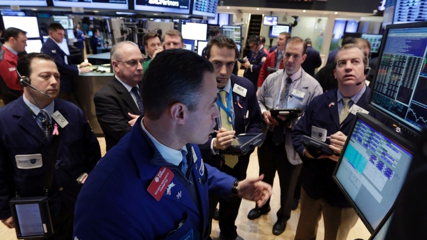 Jan. 23, 2013: Specialist Jason Hardzewicz, foreground, works at the post that trades Coach and Textron, on the floor of the New York Stock Exchange.