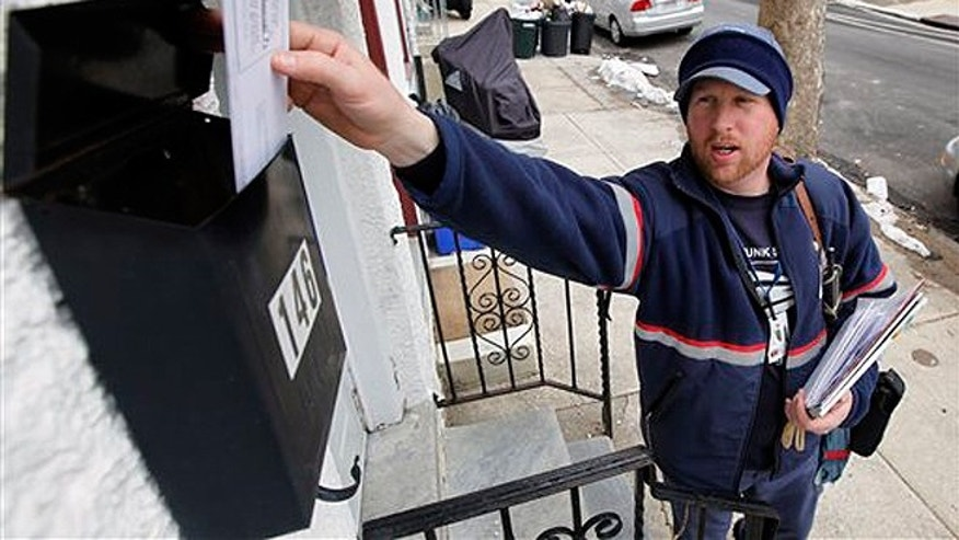 FILE - March 2, 2010: Letter carrier Kevin Pownall delivers mail in Philadelphia.