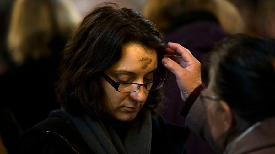 Feb. 13, 2013: A member of the faithful has her forehead marked with black ashes in the sign of the cross during a Mass for Ash Wednesday at Westminster Cathedral in London, which is the Mother Church for Roman Catholics in England and Wales.