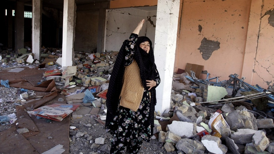 A Pakistani Shiite woman reacts at the site of a Saturday bombing which killed scores of people, in Quetta, Pakistan on Monday, Feb. 18, 2013. The families of the victims of a Saturday, Feb. 16, 2013 bombing of a market in Quetta have refused to bury their loved ones until authorities take action against the militants who were responsible. (AP Photo/Arshad Butt)