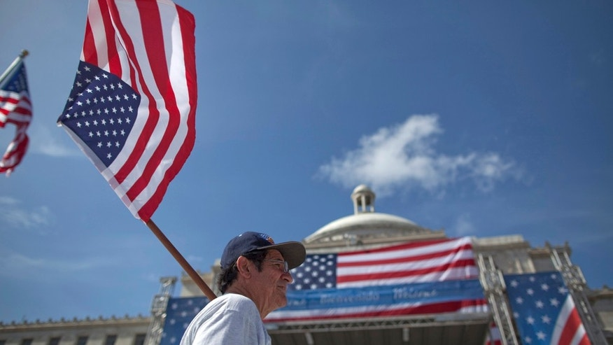 A man walks holding a US flag in front of the Capitol before the arrival of President Barack Obama in San Juan, Puerto Rico, Tuesday June 14, 2011. Obama's trip marks the first visit to Puerto Rico by a sitting U.S. President since John F. Kennedy's 1961 visit. (AP Photo/Ramon Espinosa)