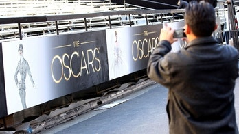 A member of the press takes a picture as preparations are made for the 85th Academy Awards in Los Angeles, Wednesday, Feb. 20, 2013. The Academy Awards will be held at the Dolby Theatre on Sunday. (Photo by Matt Sayles/Invision/AP)