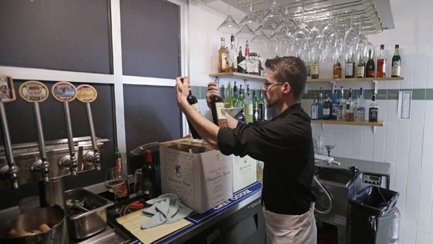 Feb. 26, 2013: Manager Dustin Humes holds wine bottles in a small room which is out of the view of patrons at Vivace Restaurant in Salt Lake City.