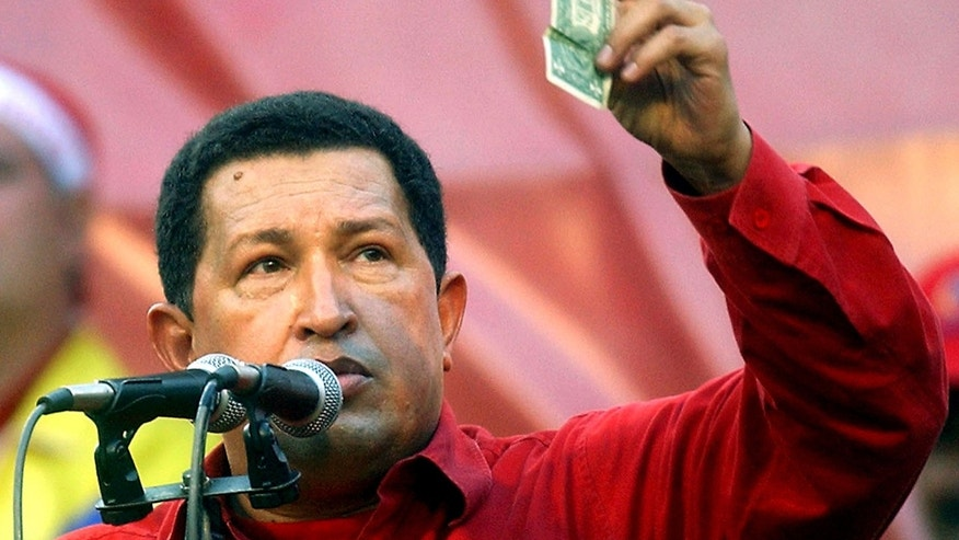 FILE - In this Jan. 23, 2005 photo, Venezuela's President Hugo Chavez holds up a U.S. dollar bill and challenges U.S. President George W. Bush to bet which of them will remain in power longer at a rally in Caracas, Venezuela. Venezuela's Vice President Nicolas Maduro announced that Chavez died on Tuesday, March 5, 2013, at age 58 after a nearly two-year bout with cancer. (AP Photo/Fernando Llano, File)