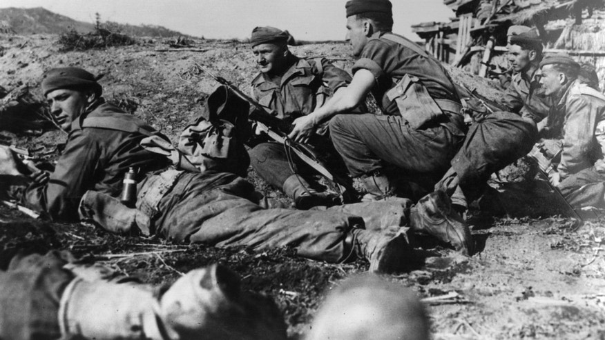 16th November 1950:  Men of the Argyle and Sutherland Highlanders take cover as they advance into the town of Chonju on the British front in North Korea during the Korean War.  (Photo by Hulton Archive/Getty Images)