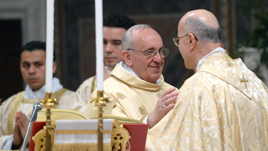 In this photo provided by the Vatican newspaper L'Osservatore Romano, Pope Francis greets Secretary of State cardinal Tarcisio Bertone, right, as he celebrates his inaugural Mass with cardinals, inside the Sistine Chapel, at the Vatican, Thursday, March 14, 2013. (AP Photo/L'Osservatore Romano, ho)