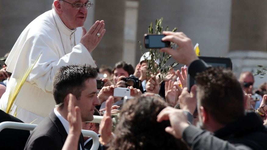 Pope Francis blows a kiss to faithful after celebrating his first Palm Sunday Mass in St. Peter's Square at the Vatican, Sunday, March 24, 2013.