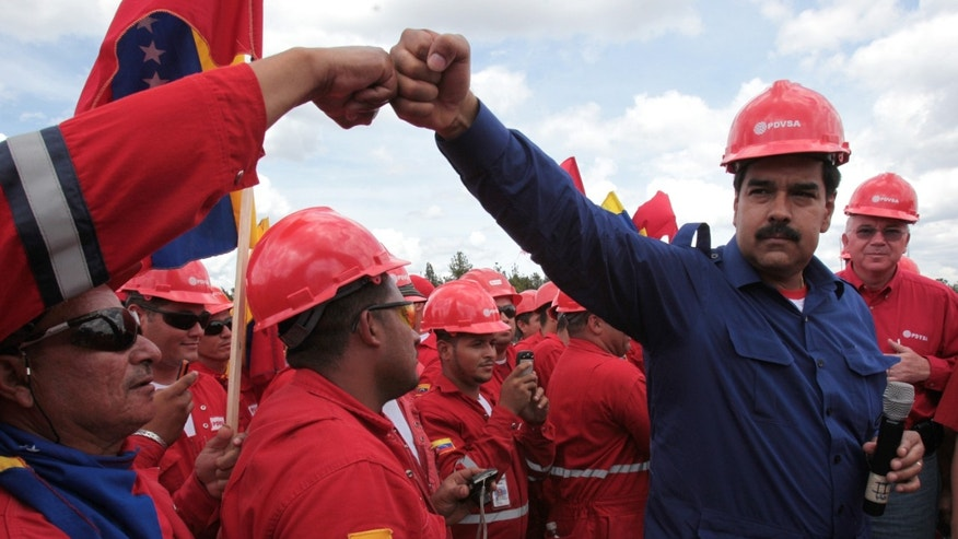 The candidate for president of Venezuela Nicolas Maduro greets a worker during a visit to a state oil company PDVSA's facility  in the Orinoco Basin March 21, 2013.  (AP Photo/Miraflores Presidential Office)