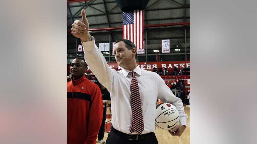 Jan. 28, 2012: In this file photo, Rutgers coach Mike Rice waves as he holds a ball presented to him for his 100th career win after Rutgers defeated Cincinnati in an NCAA college basketball game in Piscataway, N.J.