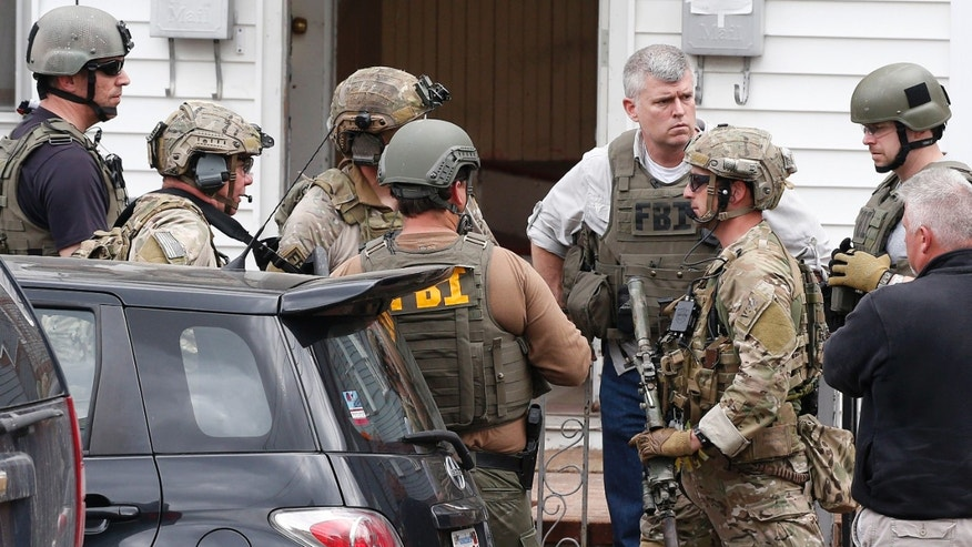 Heavily armed FBI agents gather next door to 410 Norfolk Street in Cambridge, Mass., Friday, April 19, 2013.