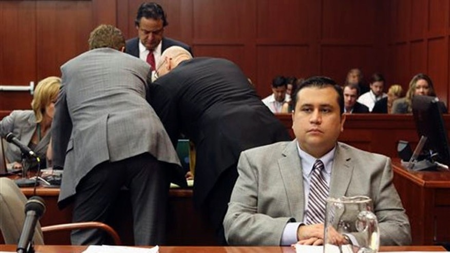 George Zimmerman sits at the defense table as his attorneys work in the background during jury selection at his trial in Seminole circuit court in Sanford, Fla., Friday June 14, 2013.
