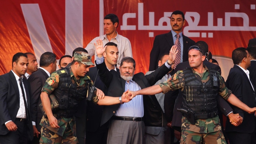 FILE - June 29, 2012: Egypt's President-elect Mohammed Morsi waves to supporters after giving a speech at Tahrir Square in Cairo.