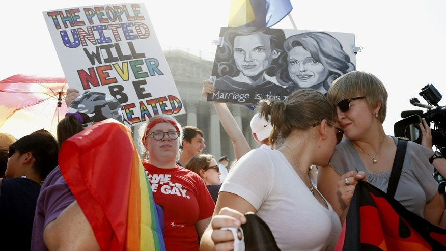 American University students Sharon Burk, left, and Molly Wagner participate in a rally for rights for gay couples in front of the Supreme Court in Washington.