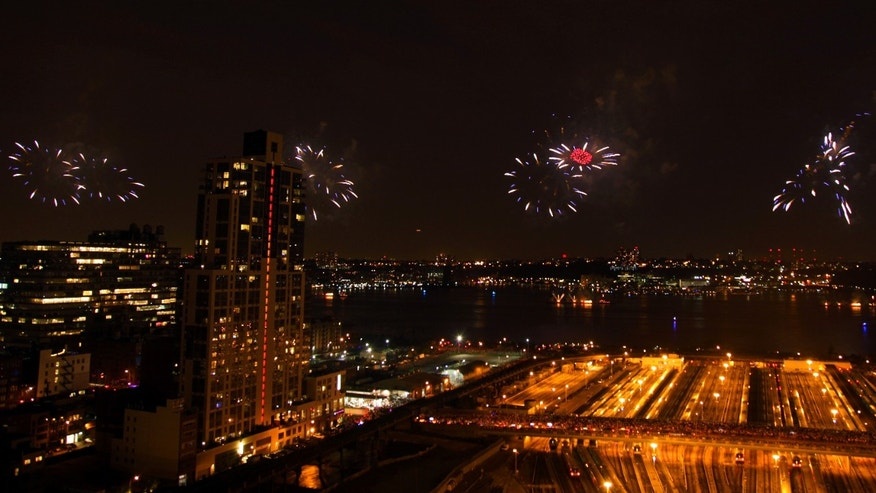 FILE -- July 4, 2012: Spectators watch over Hudson Yard in New York as fireworks light up the sky over the Hudson River during the Macy&#39&#x3b;s Fourth of July fireworks show.