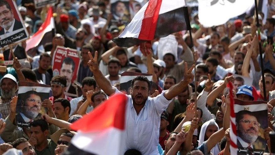 "Egyptian supporters of deposed president Mohamed Morsi shout slogans during a rally outside Cairo's Rabaa al-Adawiya mosque on July 8, 2013. Morsi's Muslim Brotherhood, which has led demonstrations against Wednesday's overthrow of the Islamist leader, called for an ""uprising,"" saying troops and police ""massacred"" its supporters during dawn prayers in Cairo Monday."
