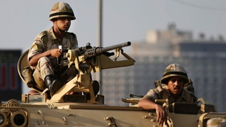 July 8, 2013: Egyptian army soldiers take their positions on top of their armored vehicle to guard the entrances of Tahrir square, in Cairo.