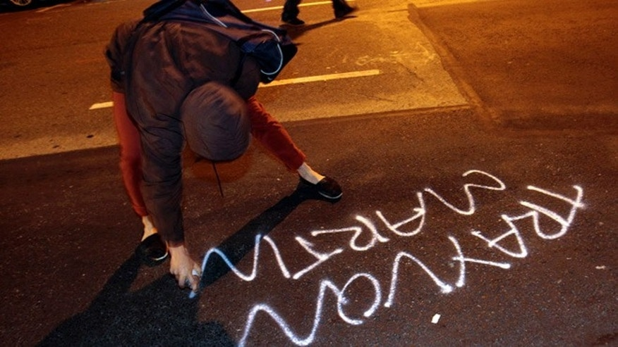 July 14, 2013: A woman spray paints along Franklin Street during a protest after George Zimmerman was found not guilty in the 2012 shooting death of teenager Trayvon Martin, early Sunday in Oakland, Calif.