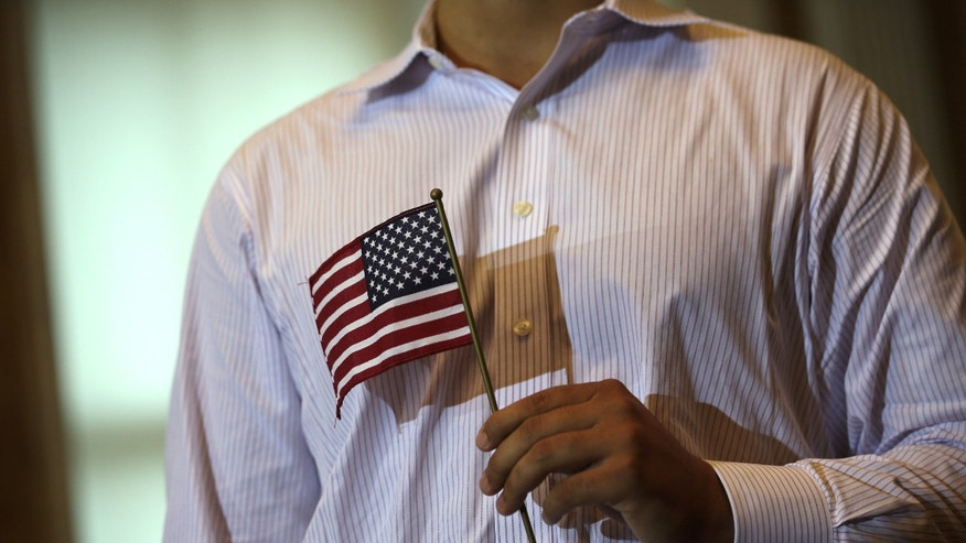 WASHINGTON, DC - JULY 03:  A new U.S. citizen holds a U.S. flag during a naturalization ceremony at the Treasury Department July 3, 2013 in Washington, DC. More than 7,800 people will become citizens at more than 100 special ceremonies, as part of the United States Citizenship and Immigration Services' (USCIS) annual celebration of Independence Day, across the country and around the world from July 1 to July 5.  (Photo by Alex Wong/Getty Images)