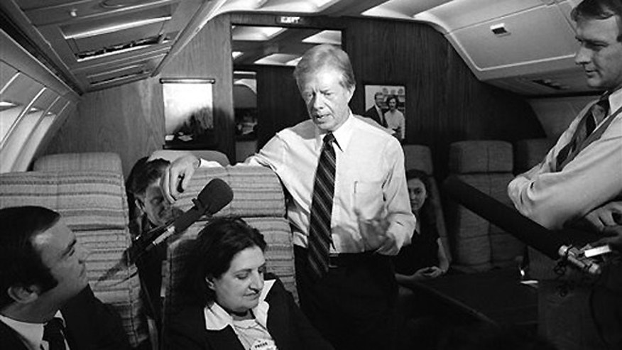 FILE -Oct. 20, 1979: President Jimmy Carter and press secretary Jody Powell, right, talk with reporters Helen Thomas, center, and Sam Donaldson, left, while aboard Air Force One prior to landing at Andrews Air Force Base, Md.