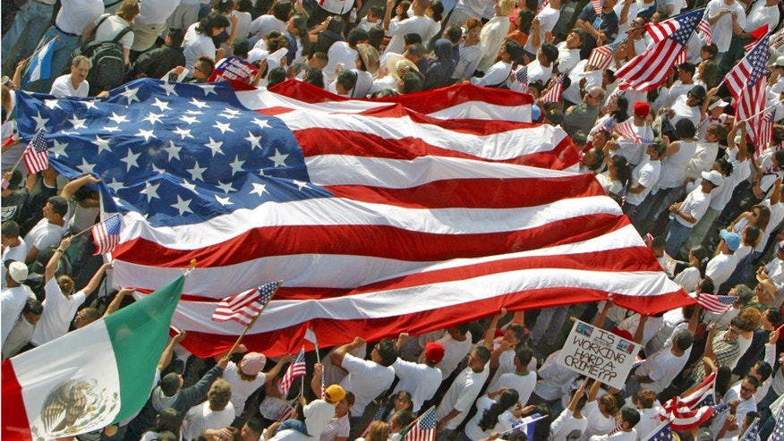 Demonstrators hold U.S. flags along Wilshire Blvd., during an immigration rally near La Brea Avenue in Los Angeles, Monday, May 1, 2006. More than 1 million mostly Hispanic immigrants and their supporters skipped work and took to the streets Monday, flexing their economic muscle in a nationwide boycott that succeeded in slowing or shutting many farms, factories, markets and restaurants. (AP Photo/Stefano Paltera)
