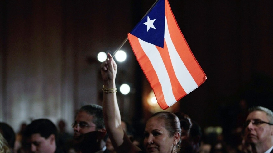 MIAMI, FL - JANUARY 27:  Elizabeth Cuevas-Neunder holds a Puerto Rican flag as she listens to Republican presidential candidate and former Speaker of the House Newt Gingrich speak after he was endorsed by the National Hispanic Leadership Network at the Doral Golf Resort and Spa on January 27, 2012 in Miami, Florida. Gingrich is campaigning ahead of Florida's January 31, primary.  (Photo by Joe Raedle/Getty Images)