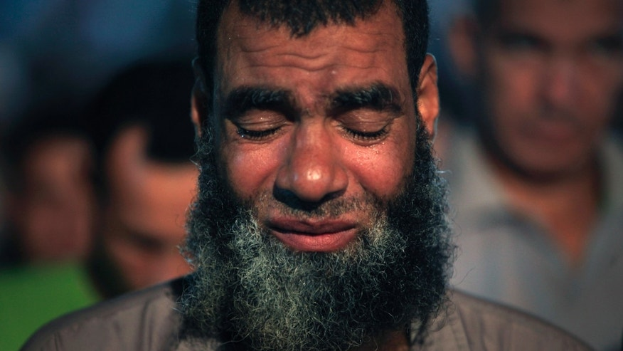 A supporter of Egypt's ousted President Mohammed Morsi cries while praying outside Rabaah al-Adawiya mosque, where protesters have installed a camp and hold daily rallies at Nasr City in Cairo, Egypt, Sunday, Aug. 4, 2013. (AP Photo/Khalil Hamra)