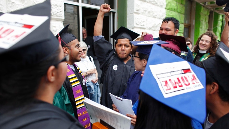"""Dreamers"" wearing school graduation caps and gowns gather outside a restaurant where they prepared legal documents before walking to the U.S. port of entry to request humanitarian parole, in Nogales, Mexico, Monday, July 22, 2013."