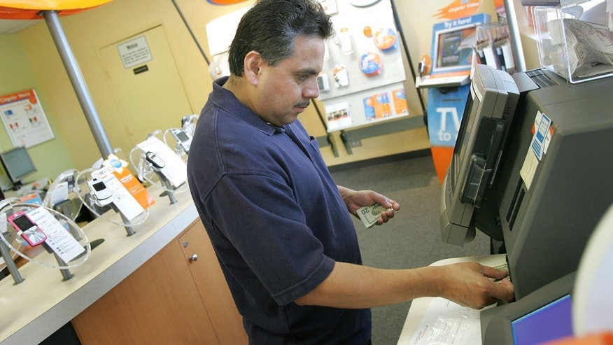 "ELMHURST, IL - JUNE 12: Mexican-American Alberto Mejia pays his Cingular phone bill at a Cingular store June 12, 2006 in Elmhurst, Illinois. Cingular, the largest wireless carrier in the nation, is reportedly converting 420 of their stores in more than 40 cities in the US to, as Cingular says, ""a bilingual concept,"" in that the stores will have both English and Spanish phone information, payment options and bilingual staff members. This Elmhurst store is one of the converted stores. (Photo by Tim Boyle/Getty Images)"