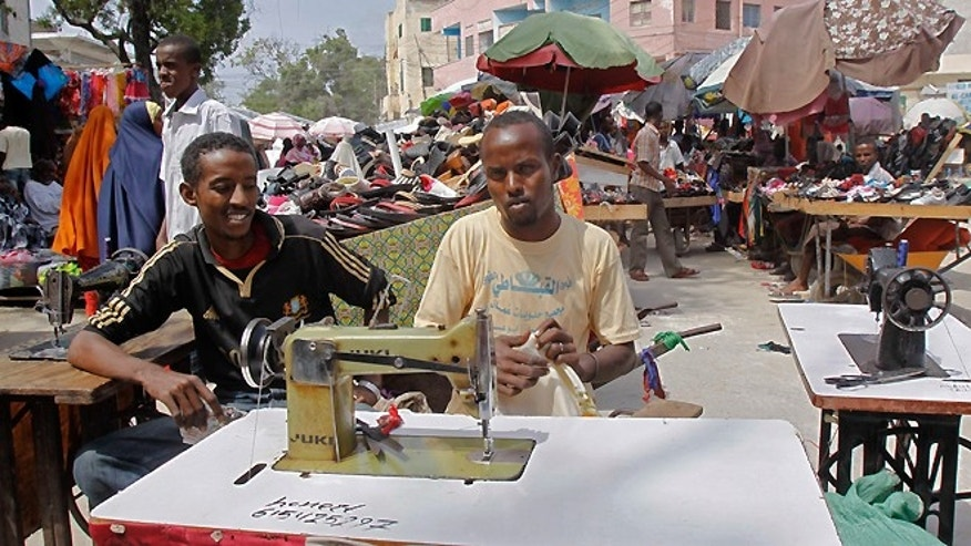 FILE -- July 22, 2013: A Somali tailor sews cloth in the open-air Hamarweyne market of Mogadishu, Somalia.