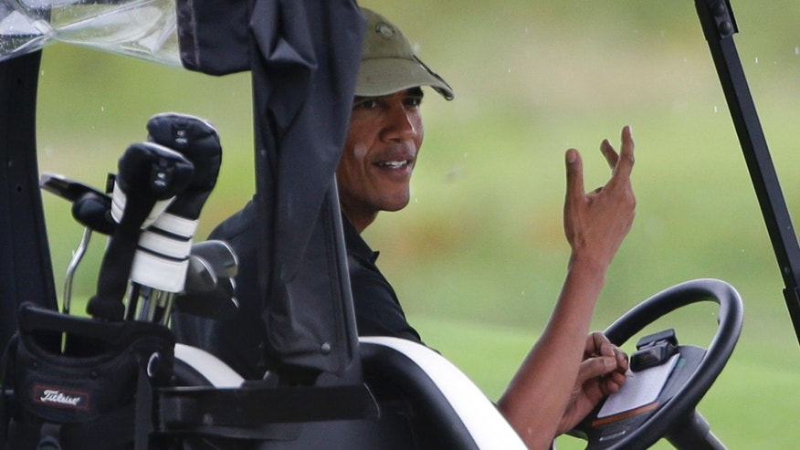 President Barack Obama gestures from his golf cart off while golfing at Vineyard Golf Club in Edgartown, Mass., on the island of Martha&#39&#x3b;s Vineyard Sunday, Aug. 18, 2013. (AP Photo/Steven Senne)
