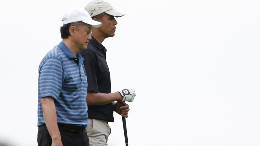 President Barack Obama, right, stands with World Bank President Jim Kim, left, while golfing at Vineyard Golf Club in Edgartown, Mass., on the island of Martha's Vineyard Sunday, Aug. 18, 2013.  Obama returned to the golf course Sunday to play his sixth and final round of a weeklong vacation on Martha's Vineyard.  (AP Photo/Steven Senne)