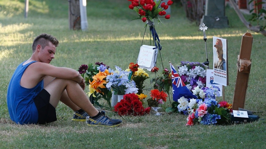 Twenty-three year old Aaron Boyer, who lives nearby, sits by the memorial for slain Australian Christopher Lane while out for a run in Duncan, Okla., Tuesday, Aug. 20, 2013. Lane, who was on a baseball scholarship at East Central University in Ada, Okla., was in Duncan, Okla., visiting his girlfriend, when he was shot and killed Friday, Aug. 16, 2013.(AP Photo/Sue Ogrocki)