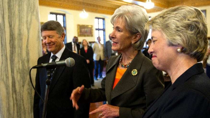 County Judge Ed Emmett, left, and Mayor Annise Parker, right, look on as Secretary of Health and Human Services, Kathleen Sebelius, center, addresses attendees during a stakeholder meeting to address implementation of the Affordable Care Act, Monday, Aug. 19, 2013, in Houston. (AP Photo/Houston Chronicle, Cody Duty)