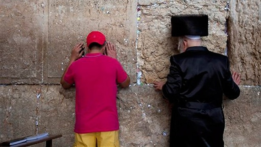 Sept. 4, 2013: An ultra-Orthodox Jewish man prays alongside a tourist ahead of the Jewish New Year at the Western Wall, the holiest site where Jews can pray in Jerusalem's old city.