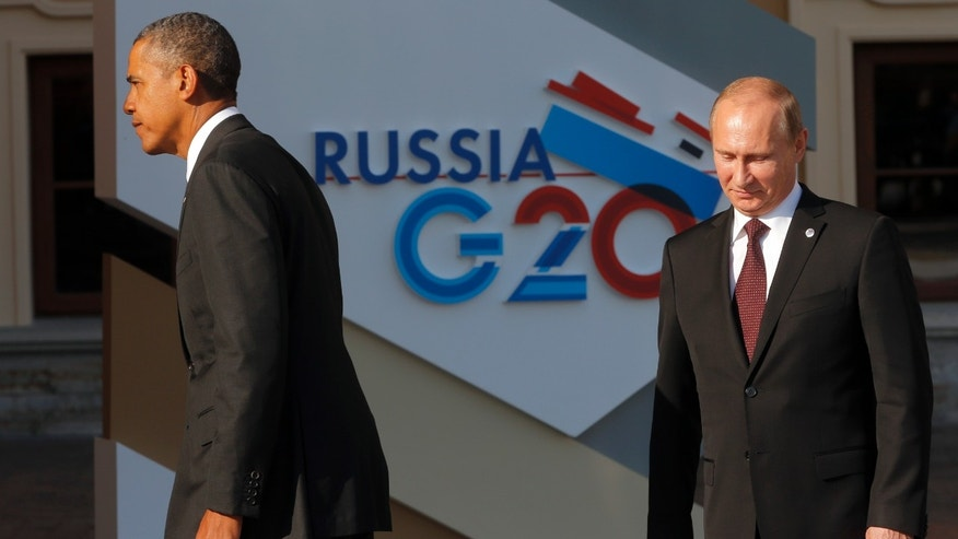 U.S. President Barack Obama, left, walks away after shaking hands with Russia's President Vladimir Putin during arrivals for the G-20 summit at the Konstantin Palace in St. Petersburg, Russia on Thursday, Sept. 5, 2013. The threat of missiles over the Mediterranean is weighing on world leaders meeting on the shores of the Baltic this week, and eclipsing economic battles that usually dominate when the G-20 world economies meet. (AP Photo/Dmitry Lovetsky)