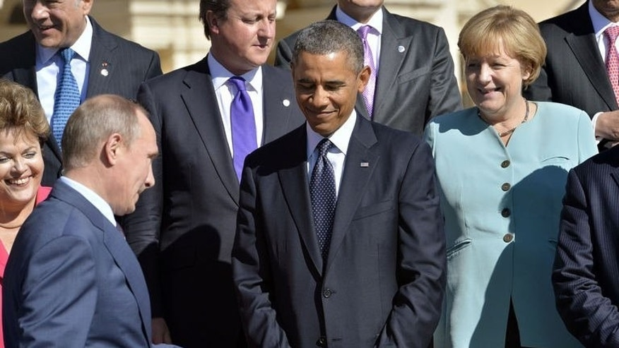 Russian President Vladimir Putin walks past his US counterpart Barack Obama ahead of a family photo for the G20 summit in Saint Petersburg, on September 6, 2013. World leaders at the G20 summit have failed to bridge their bitter divisions over US plans for military action against the Syrian regime, with Washington signalling it has given up on securing Russia's support at the UN on the crisis.