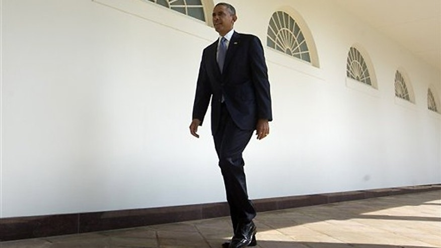 Sept. 10, 2013: President Obama walks along the West Wing Colonnade toward the Oval Office of the White House in Washington,  ahead of his daily briefing.