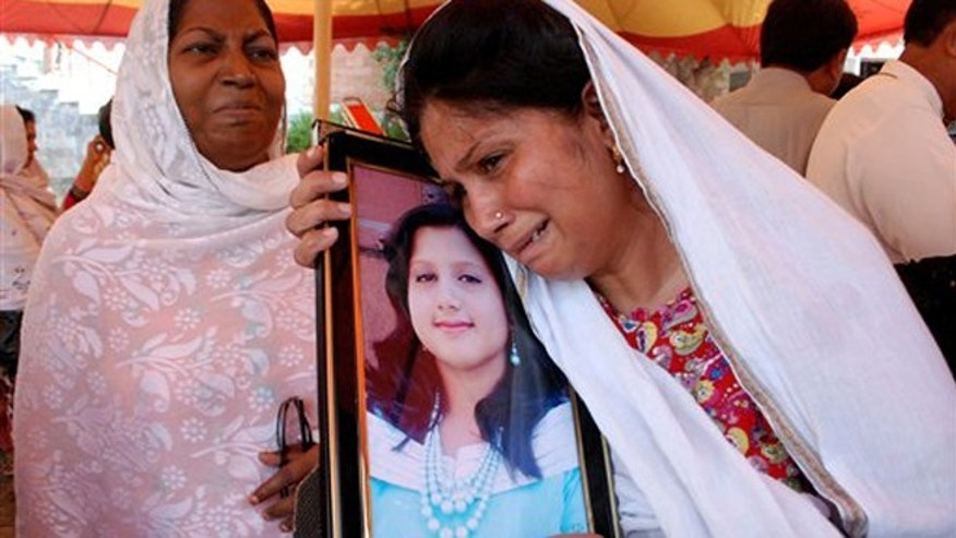 Sept. 24, 2013: A Pakistani Christian mother holds a picture of her daughter, who lost her life in a suicide bombing of the All Saints Church in the northwestern city of Peshawar, Pakistan. Pakistani Christians denounced the deadliest attack ever in this country against members of their faith when a pair of suicide bombers blew themselves up amid hundreds of worshippers outside a historic church in northwestern Pakistan on Sunday, Sept. 22, 2013.