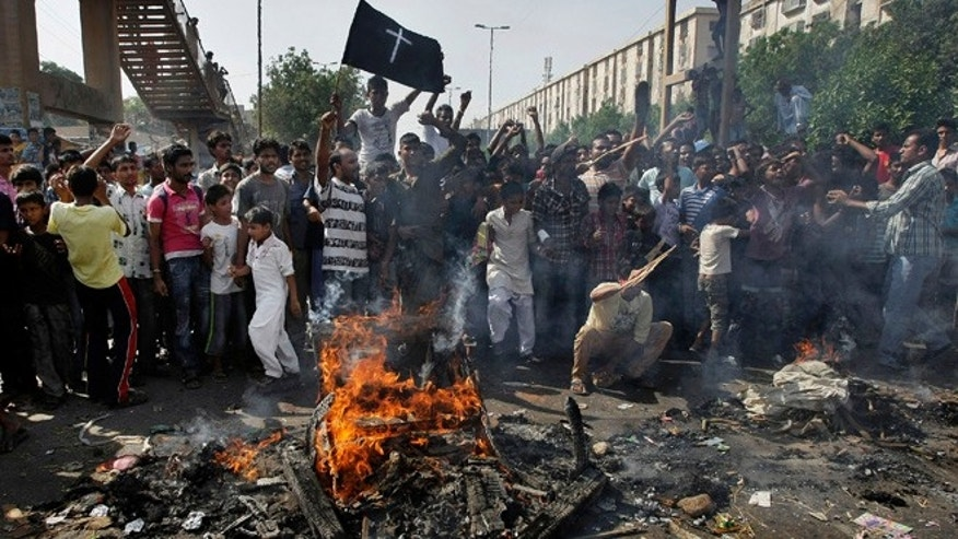 Sept. 22, 2013: Pakistani Christians chant slogans as they burn materials during a protest against a suicide attack on a church in Karachi, Pakistan. A suicide bomb attack on a historic church in northwestern Pakistan killed scores of people Sunday, officials said, in one of the worst assaults on the countrys Christian minority in years.
