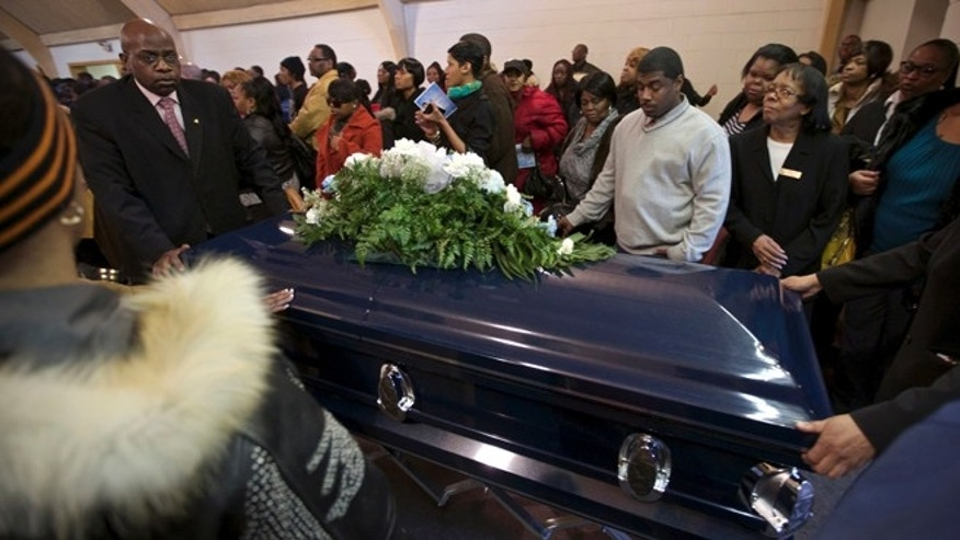 Funeral directors wheel the casket of Ronnie Chambers, 33, a victim of gun violence, following his funeral in Chicago February 4, 2013.