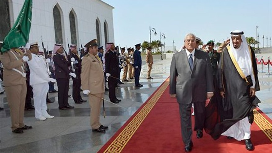 FILE -- Oct. 7, 2013: In this photo released by the Saudi Press Agency, Defense Minister and Saudi Crown Prince Salman bin Abdul-Aziz, right, welcomes Egyptian interim President Adly Mansour on his arrival to the airport in Jiddah, Saudi Arabia. Egypt's interim president has landed in Saudi Arabia for his first foreign trip since assuming power after the ouster of the country's Islamist president.