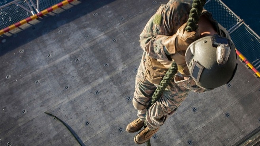 A Marine with the Force Reconnaissance Platoon, Maritime Raid Force, 31st Marine Expeditionary Unit, fast ropes out of a MV-22 Osprey aircraft on to the elevator below the flight deck August 10.